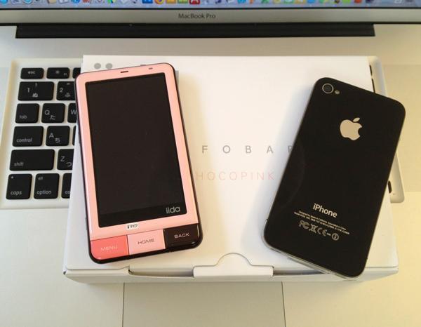 INFOBAR A01の新色チョコピンクとiPhone 4が並んでます。